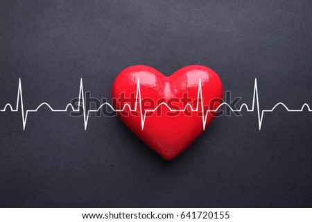 Tachycardia palpitation cardiogram with red heart on black background. Top view, copy space.