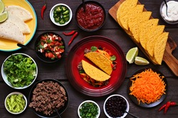 Taco bar table scene with a selection of ingredients. Above view on a dark wood background. Mexican food buffet.
