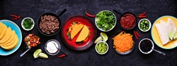Taco bar table scene with a selection of ingredients. Top view on a dark slate banner background. Mexican food buffet.