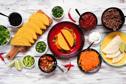 Taco bar table scene with a variety of ingredients. Above view on a rustic white wood background. Mexican food buffet.