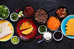 Taco bar table scene with a variety of ingredients. Overhead view on a dark slate background. Mexican food buffet.