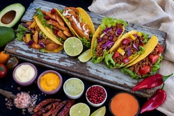 Taco with beef, pork and chicken. Variations of tacos. Mexican traditional cuisine.