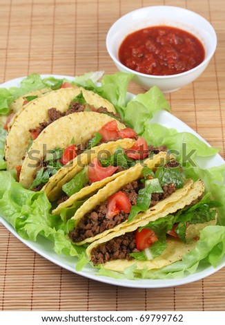 Tacos on a bed of lettuce on a serving plate