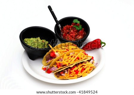 Tacos with cheese, ground beef, tomatoes and onions with guacamole and fresh salsa on the side isolated on white