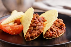 Tacos with chili con carne, tomato, and pickled baby corns