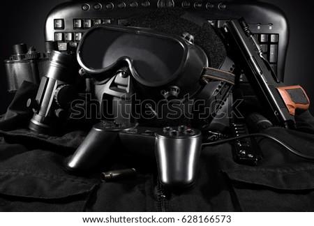 Tactical gear & gamepad.Tactical helmet, gloves, gun, binoculars laying on a jacket with gamepad & keyboard on background.