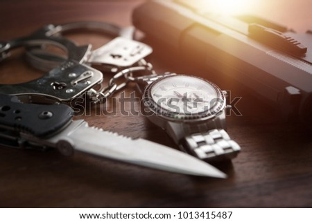Tactical gear set of Pistol gun knife handcuff and clock on wooden background. Police or military equipment concept.