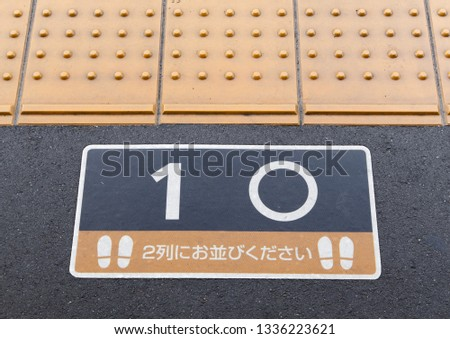 Tactile paving and rectangle warning sign on the floor of Japanese train station's platform. On the sign is Japanese language, translate : Please line up in two rows. #1336223621