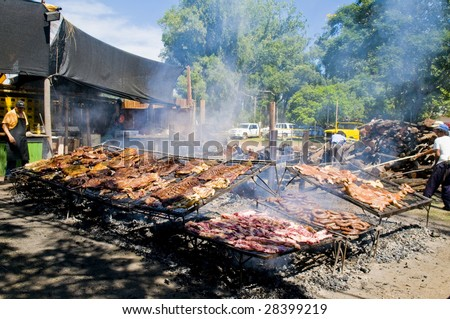 "TACUAREMBO, URUGUAY - MAR 7 : Cooks prepare barbecue in the annual festival ""Patria Gaucha"" March 7, 2009 in Tacuarembo. It is one of the biggest festival in South America to celebrate gaucho culture. - stock photo"