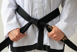 Taekwon-do woman tying her black belt and getting ready for training.