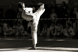 Taekwondo martial art. A young man in kimano demonstrates a kick. The inscription on the jacket
