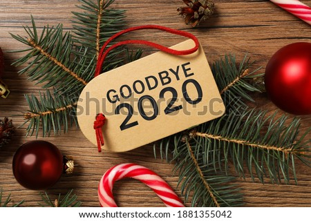 Tag with text Goodbye 2020 and festive decor on wooden background, flat lay
