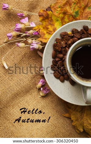 Tag with words hello autumn and the cup of coffee lying on the book with dry yellow maple leaves and everlasting flowers on sackcloth background