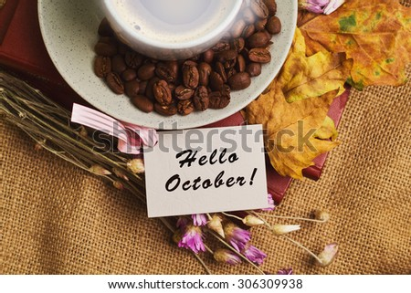 Tag with words hello october and the cup of coffee lying on the books with dry yellow maple leaves and everlasting flowers on sackcloth background