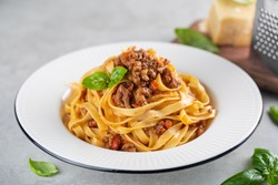 Tagliatelle al ragu - italian pasta with meat bolognese sauce. High angel. Extra hard cheese on background.