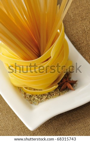 tagliatelle pasta and spaghetti with rosemary on white plate - stock photo
