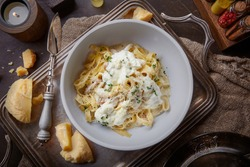 Tagliatelle pasta with different types of cheeses. Pasta with parmesan and burrata cheese on a vintage tray on a dark table among spices and chunks of crushed parmesan. Spaghetti with cheese
