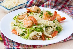 Tagliatelle pasta with fried shrimps, cheese Parmesan, parsley and zucchini ribbons, dish of restaurant