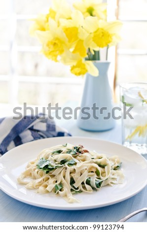 Tagliatelle pasta with pesto on white plate