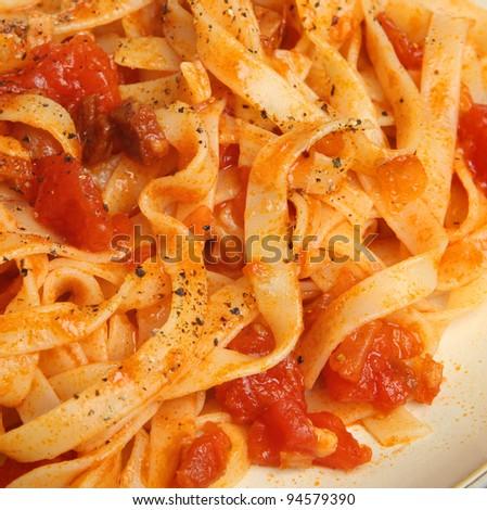 Tagliatelle pasta with tomato ragu and freshly ground pepper.