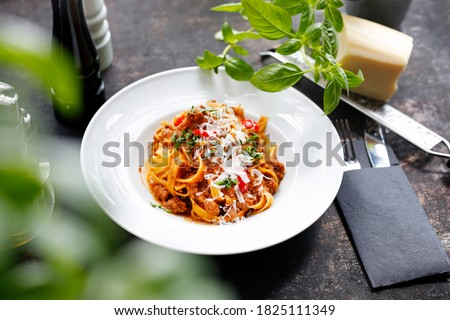 Tagliatelle with bolognese sauce, pasta with tomato sauce, and cheese. Traditional Italian cuisine. Appetizing dish served on a white plate. culinary photography. Stock photo ©