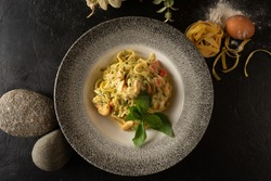 Tagliatelle with shrimp vegetables and basil. Hot dish of pasta and seafood on a dark background.