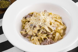 Tagliatelle with tail steak stripe and champignons with grated parmesan cheese