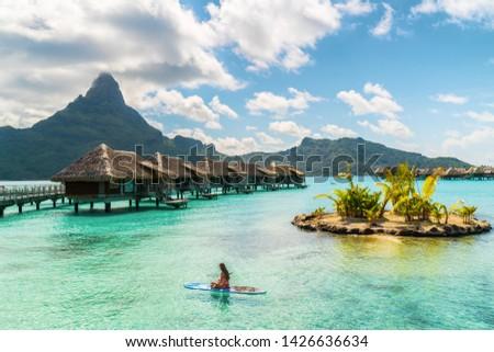 Tahiti luxury resort hotel in Bora Bora ,French Polynesia. Paddleboard leisure activity SUP paddle woman on active vacation in Tahiti, French Polynesia. Mount Otemanu summer holiday.