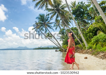Tahiti luxury travel beach vacation woman walking in polynesian cover-up skirt beachwear on idyllic paradise island in French Polynesia. Red traditional clothes, bikini and flower girl.