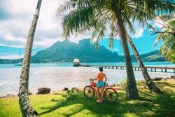 Tahiti travel biking tourist on electric bicycle rental in Bora Bora island , French Polynesia eco-tourism summer vacation adventure fun cyclist girl relaxing at landscape on E-bike biking.