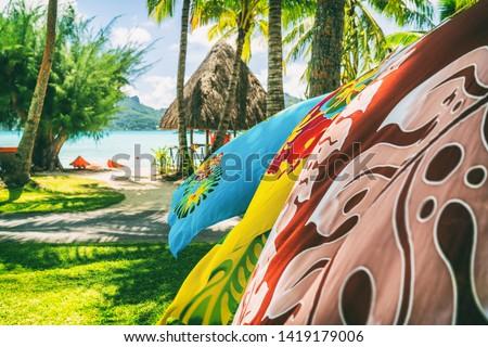 Tahiti vacation background saron pareo tahitian skirts flowing in the wind at beach resort souvenir shop of hotel. Sarong wrap skirt, Tahiti, French Polynesia. Handmade tourism souvenir. #1419179006
