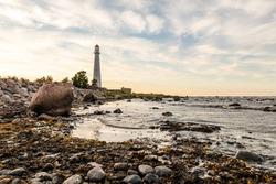Tahkuna lighthouse on the coast during sunset at Hiiumaa, Estonia, Europe. White lighthouse with red top on the rocky beach. Sun is setting near lighthouse on the shore.