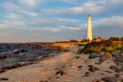 Tahkuna lighthouse on the rocky shore during sunset at Hiiumaa, Estonia, Europe. White lighthouse with red top at sundown. Pink dawn near lighthouse on the windy coast.