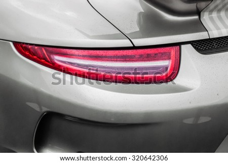 Tail light of sport grey car with rain drops and shadows. Closeup headlights of car. Modern luxury car close-up banner background. Concept of expensive, sports auto Closeup headlights Porsche 911 #320642306