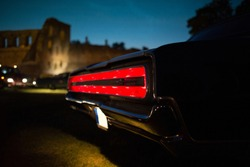 Taillight of old classic muscle car is switched on at the night