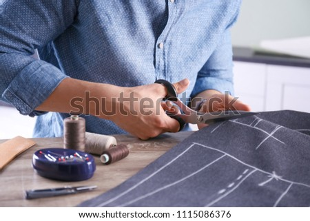 Tailor cutting fabric at table in atelier, closeup Foto stock ©