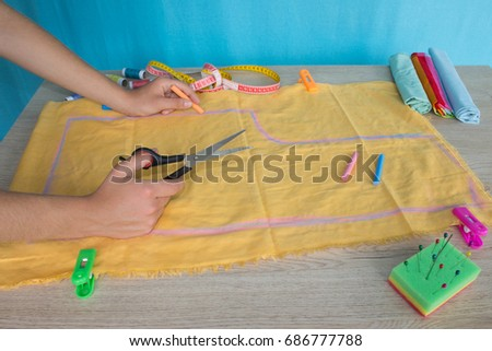 Tailor cutting fabric using large scissors or shears as he follows the chalk markings of the pattern, close up of his hands. Woman's Hand Sewing Quilt #686777788