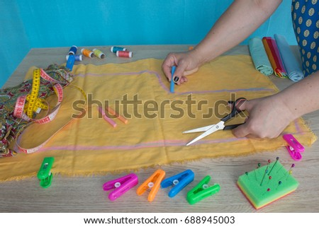 Tailor cutting fabric using large scissors or shears as he follows the chalk markings of the pattern, close up of his hands. Woman's Hand Sewing Quilt #688945003