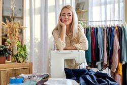 tailor making a garment in her workplace, stand in contemplation looking at camera, blond female have rest. hobby sewing as a small business concept. in bright modern room. fashion, style concept
