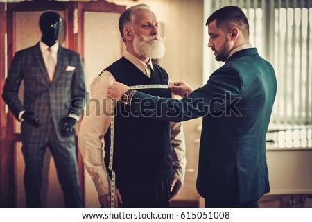 Tailor measuring client for custom made garment #615051008