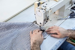 Tailor stitched seat fabrics. Close-up on man working with her sewing machine stitching a long length of fabric.