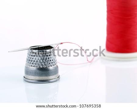Tailor tools. Needle, thread, thimble.