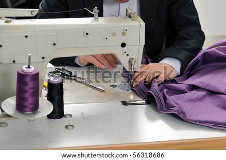 Tailor using industrial sewing machine - a series of TAILOR related images. - stock photo