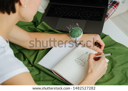 Tailor woman is sitting behind the desk, drawing sketch of a new dress, checking with her laptop at workshop. Turning ideas into clothing. She wearsc pin cushion bracelet. High angle, from behind.