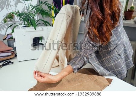 Tailor woman measuring shirt sleeve using tape meter, working in dressmaking studio showing perfect jacket layout maquette cotton Photo stock ©