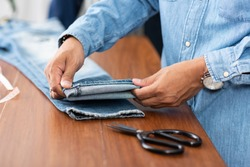 Tailor working with blue denim jeans. Tailor hem the blue jeans.