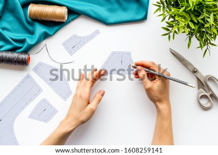 Tailor working. Women hands make patterns for clothes on white background top-down Foto stock ©