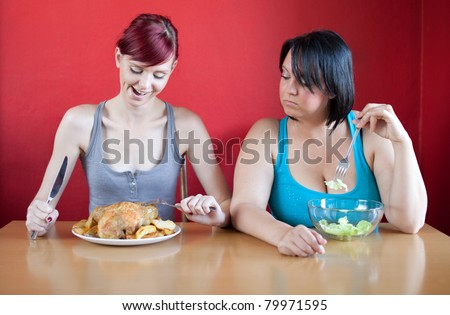 Tailored diet. Skinny woman is happy because she can eat huge meals, while the overweight woman is looking sadly at her because she has to eat just a few leaves of lettuce. Selective focus.