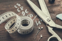 Tailoring scissors, measuring tape, thimble, including pins, chalk. Human body measurements are written on a wooden board.
