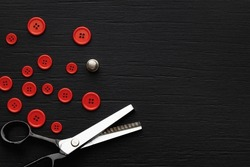 Tailoring scissors, red buttons of diferent sizes and sewing thimble finger protector on black wooden background. Textured black wooden background. Top view with copy space.